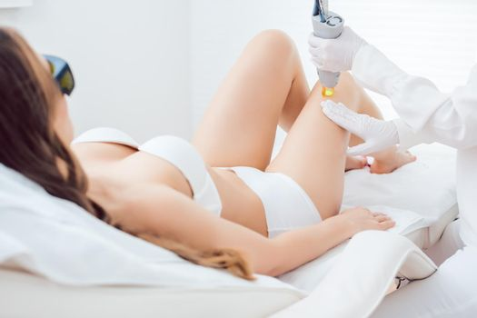 Laser hair removal therapy on a leg of woman customer