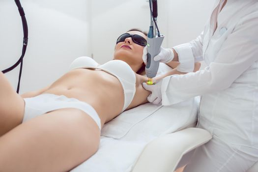 Woman during hair removal using modern laser technology