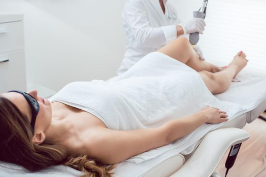 Woman in leg hair removal session at beauty parlor