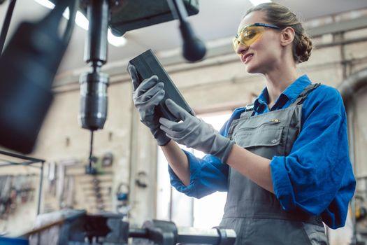 Woman in metal workshop checking workpiece