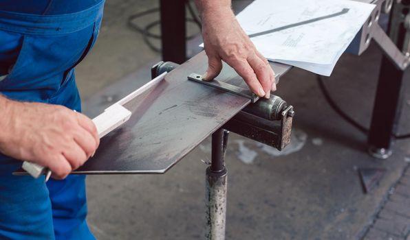 Metalworker measuring a strip of steel