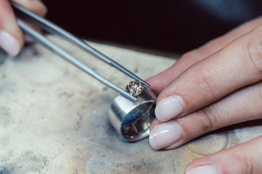 Jeweler setting a precious stone with pincers on a ring