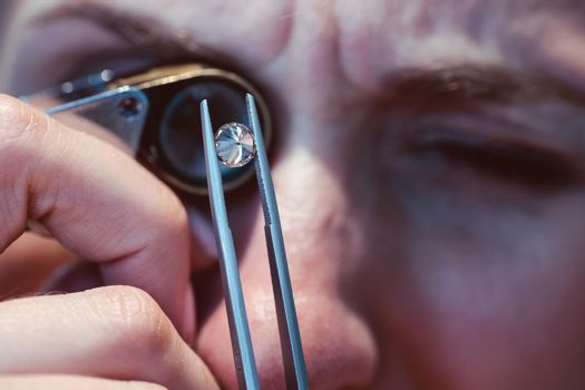 Jeweler looking at precious stone through a loupe