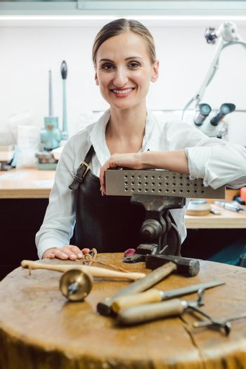 Jewelry designer in her workshop boating with her tools