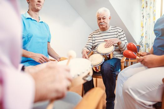 Seniors in nursing home making music with rhythm instruments