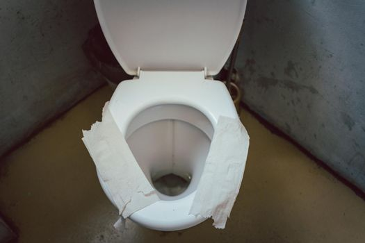 Filthy toilet seat covered with toilet paper as sit down insulation