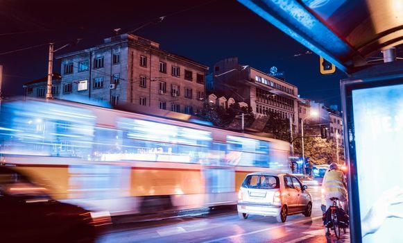 Night scene of tram in traffic with lighttrail motion blur