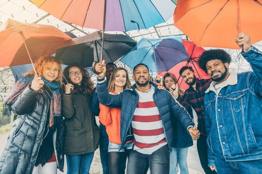 Friends making the best of rain and bad weather standing under umbrellas