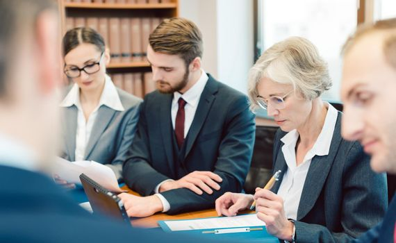 Team of partners in a law firm working diligently on a case