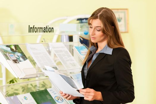 Young businesswoman reading leaflet
