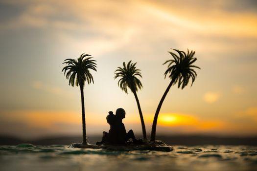 Romantic sunset scene. Fantasy landscape with little island with palms on sunset. Creative table decoration. Fantasy tropical beach. Selective focus.