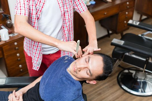 Man getting his shaved done from barber