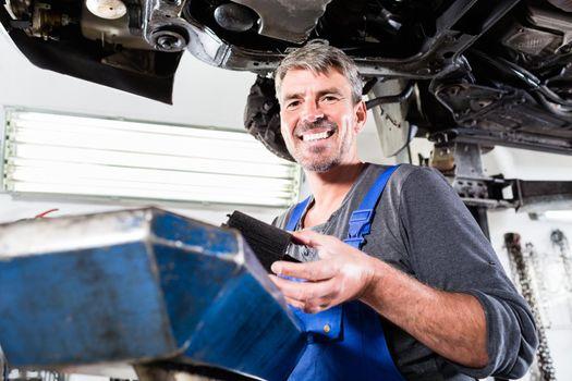 Mature mechanic holding the vehicle part