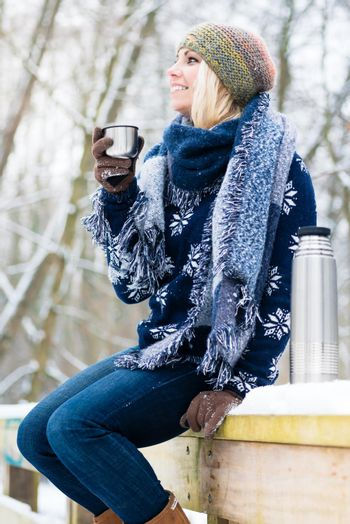 Woman freezing on a cold winter day warming herself up with hot drink