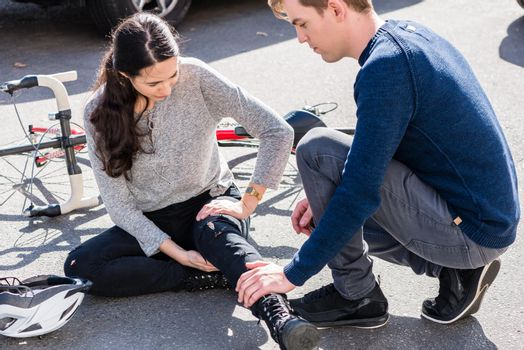 Helpful young man giving first aid to an injured woman after bicycle accident