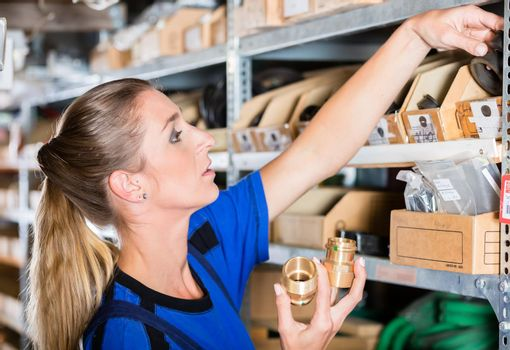 Happy worker holding a high-quality pipe fitting accessory in a sanitary shop