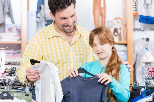 Daughter choosing t-shirt in the retail shop