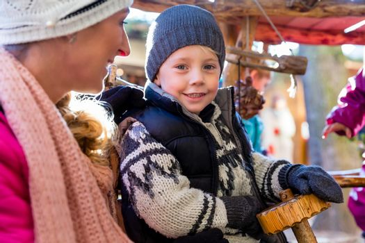 Mother with son and carousel on Christmas market