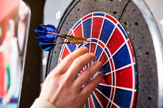 Person's hand removing arrows from dartboard