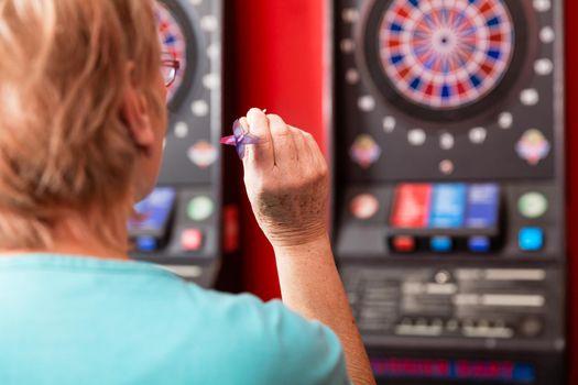 Mature woman aiming against dartboard