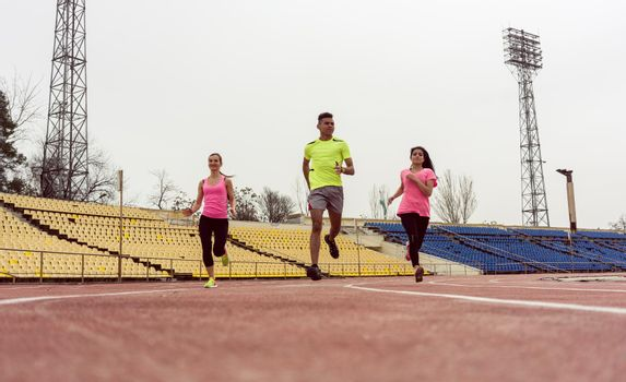 Three athlete people running in speed on sport ground