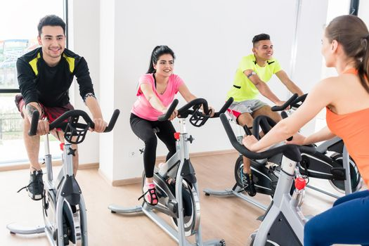 Group of young people cycling at gym
