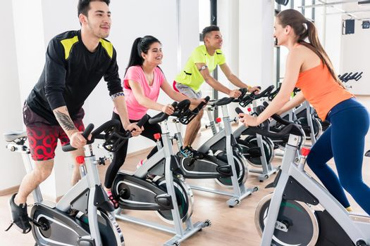 Active people exercising on bicycle at gym