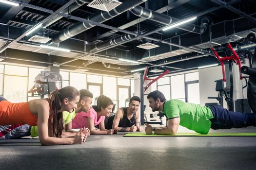 Young group of people exercising with trainer