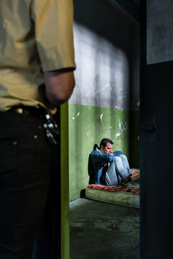 Young male prisoner sitting alone in an obsolete prison cell