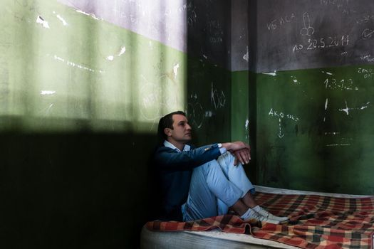 Depressed young man sitting on a mattress in a dark prison cell during custody