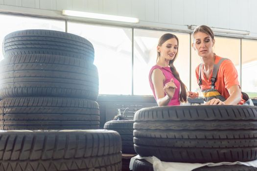 Helpful female auto mechanic checking the identification number of a tire