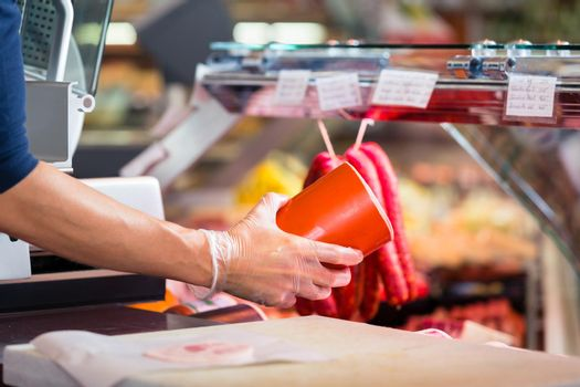 Woman in butcher shop holding sausage in her hands to sell