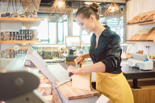 Shop clerk in deli cutting cheese