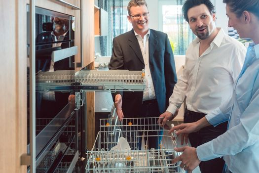 Couple checking dishwasher of new kitchen in the showroom
