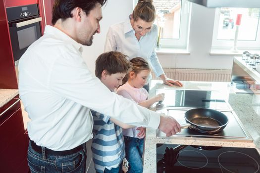 Family testing a new kitchen they intend buying in the showroom