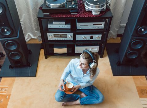 Woman listening to music from a Hi-Fi stereo