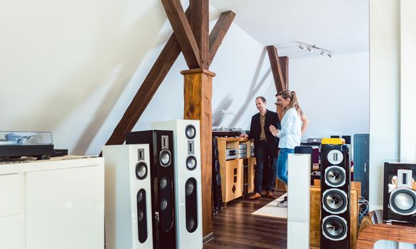 Couple buying new home stereo in Hi-Fi store