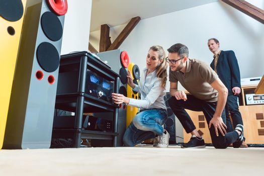 Young couple buying high-end stereo equipment in store
