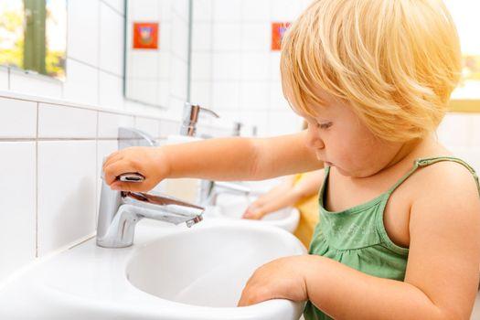 Child in kindergarten washing her hands