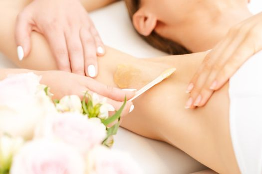 Hair removal by sugaring in a beauty salon