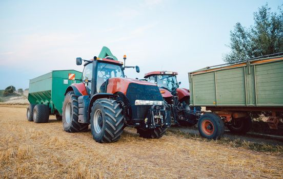 Agricultural machinery and tractor on a harvested field