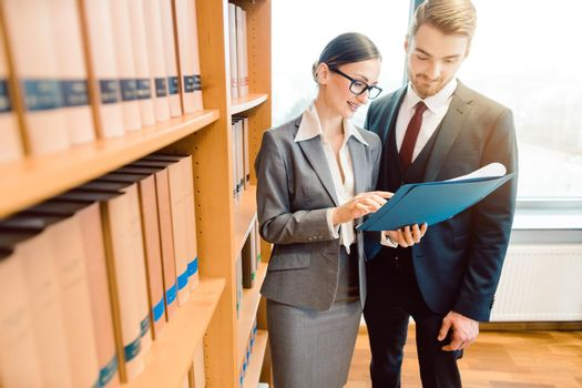Lawyers in library of law firm discussing strategy in a case holding file