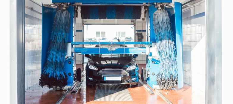 Brush turning in car wash with vehicle in it