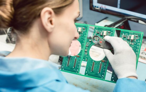 Technician soldering components to a PCB