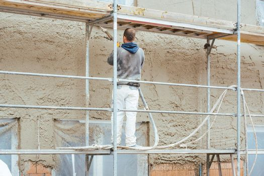 Worker plastering outer wall of newly built house