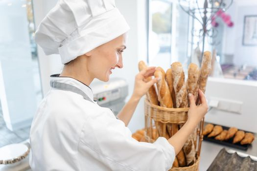 Baker woman putting bread in a basket to sell it