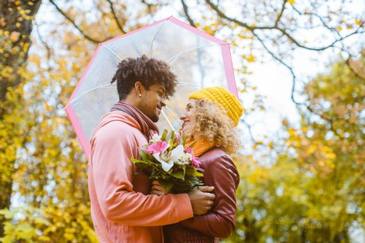 Man and woman of different ethnicity hugging in fall