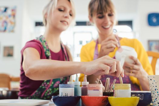Two girl friends painting their own handmade ceramics