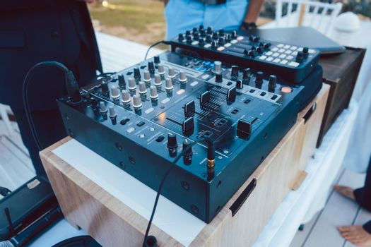 DJ mixing console at summer party