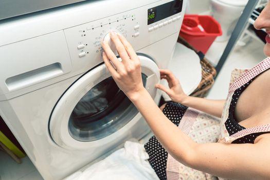 Woman homemaker operating the washing machine